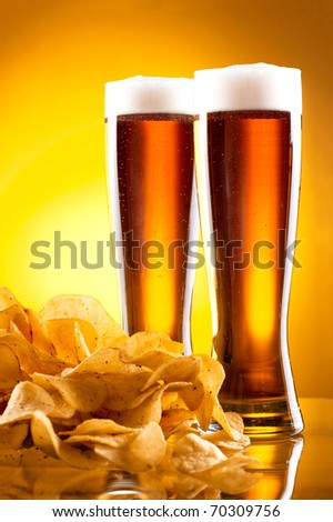 Two glass of beer and potato chips on a yellow background - stock photo