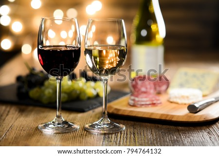 two glass of red wine and white wine with french cheese and delicatessen in restaurant wooden table with romantic dim light and cosy atmosphere