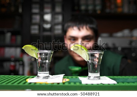 Two glass of tequila with lime at the bar