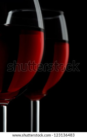 Two glassed of red wine isolated on black background - stock photo