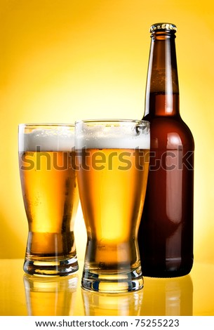 Two glasses and Bottle of fresh light beer on yellow background