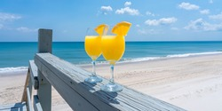 Two glasses brightly lit by the sun with a mimosa cocktail against the background of the blue sea as a symbol of comfortable relaxation