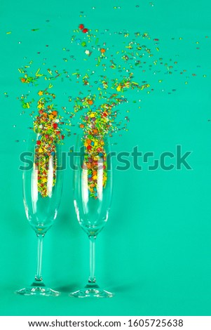 two glasses champagne roasted sprinkled colored sweets baking topping plain background holiday greetings
