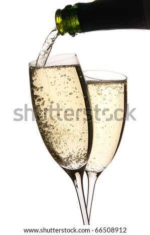 Two glasses clink in toast as sparkling wine is poured. Bubbles in the golden liquid. Isolated on white. Copy space.