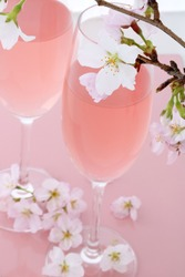 Two glasses filled with pink champagne with cherry blossoms
