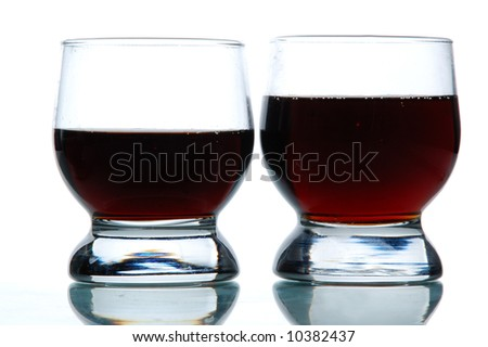 Two Glasses filled with some alcohol, white background, close-up