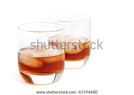 Two glasses filled with whiskey / scotch on ice cubes