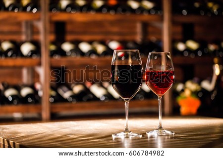 Two glasses filled with wine placed on the wooden table in fromt of the shelves with wine bottles. #606784982