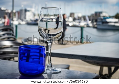 Two glasses for both water and wine on a table at a waterfront restaurant.