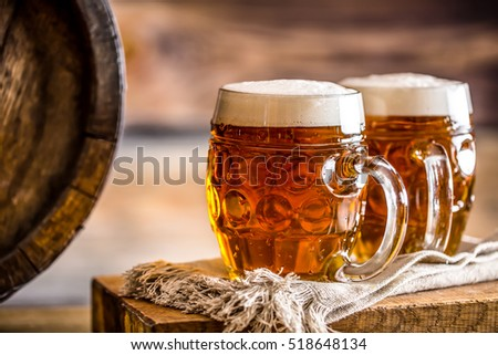 Two glasses full of beer with wooden barel.
