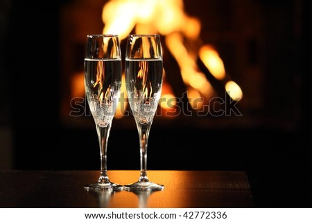two glasses in front of fireplace