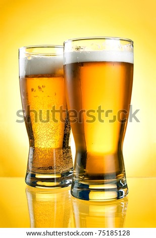 Two glasses of beer close-up with froth over yellow background