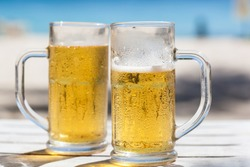 Two glasses of beer on a beach
