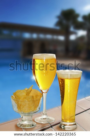 two glasses of beer with a bowl of potatoes fried in the border of a pool - stock photo