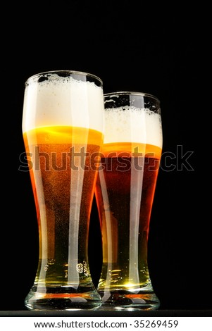 Two glasses of beer with froth over black background