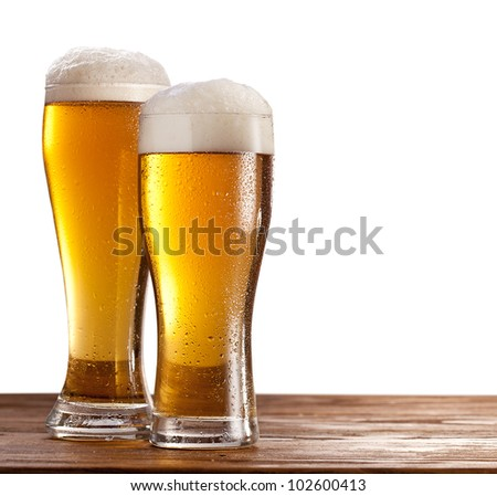 Two glasses of beers on a wooden table. Isolated on a white background.