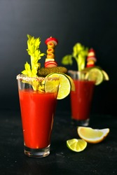 Two glasses of Bloody Mary cocktail garnishes with celery, olives, pickles, cheese and lime, black background