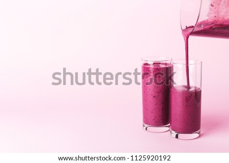 Two glasses of blueberries smoothie on pink background. Poring from blender into glass.