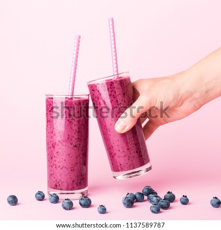Two glasses of blueberries smoothie with straws on pink background. Woman's hand holding one glass. Healthy summer drink.