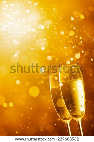 two glasses of champagne against gold bokeh background #229608562