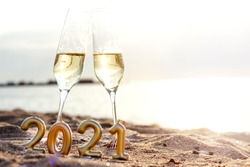 Two glasses of champagne and figures with numbers of the new year 2021 on the sand on the beach against the background of the sea. Space for text. Spend Holidays and celebration on the beach concept