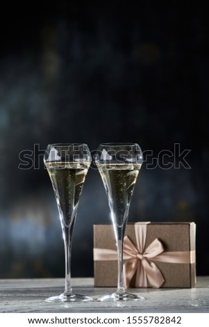 Two glasses of champagne and gift box with bronze ribbon. Copyspace for text.