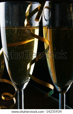 Two glasses of champagne and gold streamer over black background