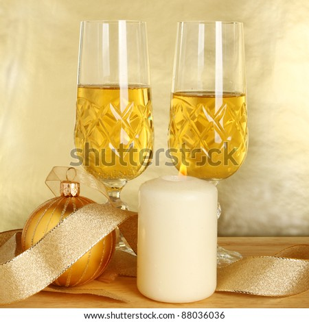Two glasses of champagne, gold ribbon and Christmas bauble with a burning candle against a gold background