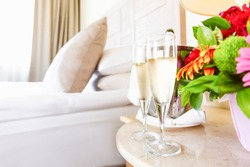 Two glasses of champagne in the upscale hotel room. Dating, romance, honeymoon, valentine, getaway concepts. Horizontal