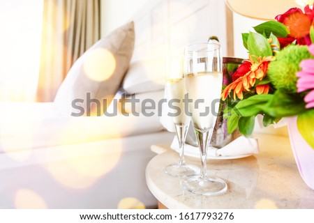 Two glasses of champagne in the upscale hotel room. Dating, romance, honeymoon, valentine, getaway concepts. Horizontal, light festive bokeh lights