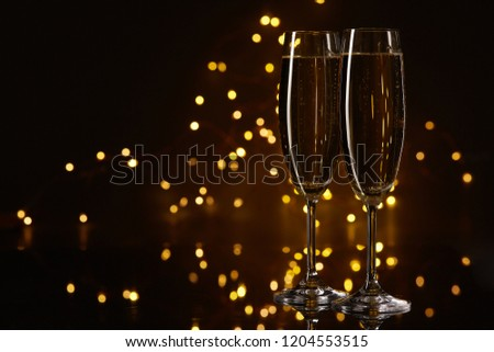 Two glasses of champagne on a dark background with LED lights garland. Copy space for text. #1204553515