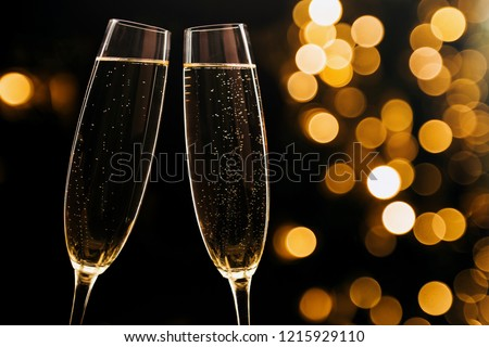Two glasses of champagne on black stylish background with golden bokeh circles. Place for text. Festive concept.