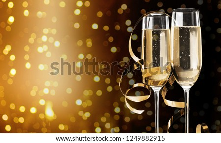 Two glasses of champagne on black stylish background with golden bokeh circles. Place for text. Festive concept. #1249882915