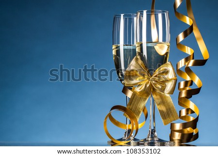 Two glasses of champagne on blue background