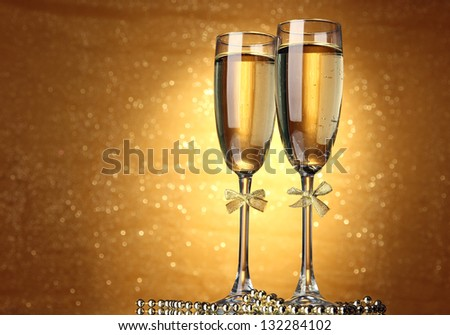 Two glasses of champagne on bright background with lights #132284102