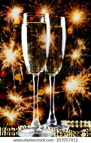 Two glasses of champagne on bright background with sparklers #307057412
