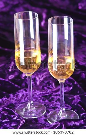 Two glasses of champagne on deep purple velvet