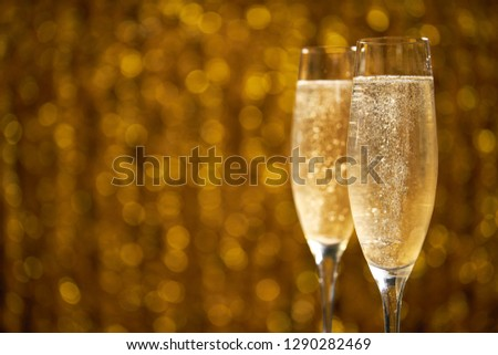 two glasses of champagne on golden stylish background with golden bokeh circles place for text #1290282469