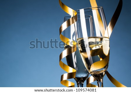 Two glasses of champagne on light blue background