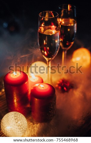 Two glasses of champagne on the background of a Christmas tree with candles in darkness with snow #755468968