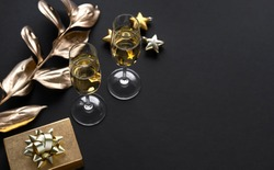 Two glasses of champagne over black background and golden Christmas decoration. Holiday decorations on dark table.