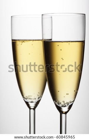 Two glasses of champagne over light gray white background