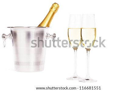 two glasses of champagne with a champagne bottle in a bucket on white background