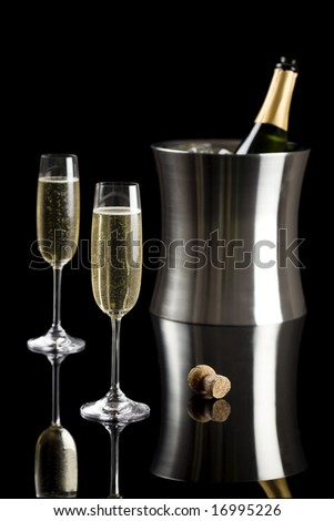 Two glasses of champagne with a stainless bucket in the background isolated on a black background