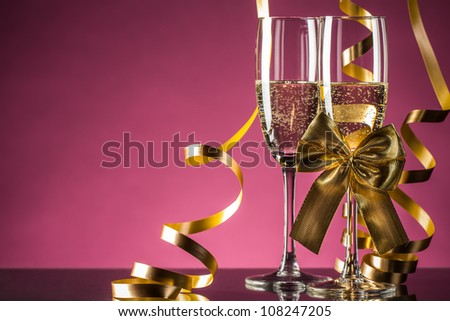 Two glasses of champagne with bow on pink background