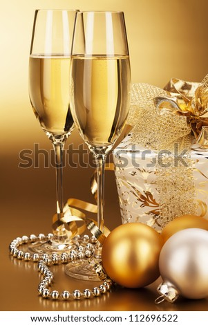 two glasses of champagne with christmas balls and a christmas present