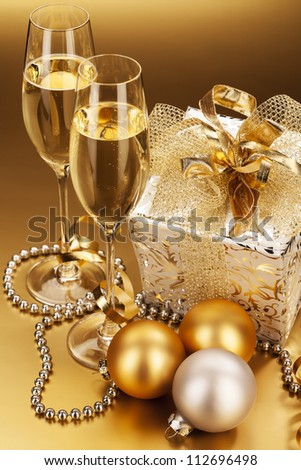 two glasses of champagne with christmas present and christmas balls