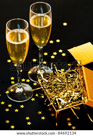 Two glasses of champagne with golden gift box