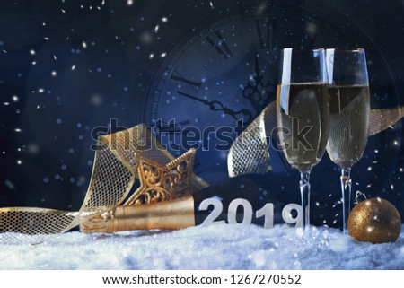 Two glasses of champagne with golden ribbon, star and ball with snow. Christmas card #1267270552