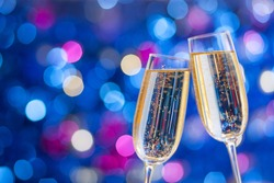 Two glasses of champagne with lights in the background. Very shallow depth of field. Selective focus.